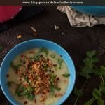 Rice congee in ablue bowl topped with fried onions
