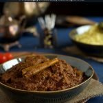 Beef rendang in a dark bowl with yellow rice in the background