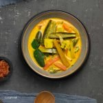 sayur lemak yellow vegetable curry in a bowl