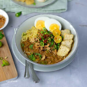 mee rebus (egg noodles) topped with eggs, tofu, chillies limes and gravy