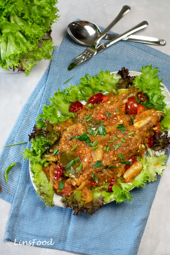 fish covered in red sauce with salad