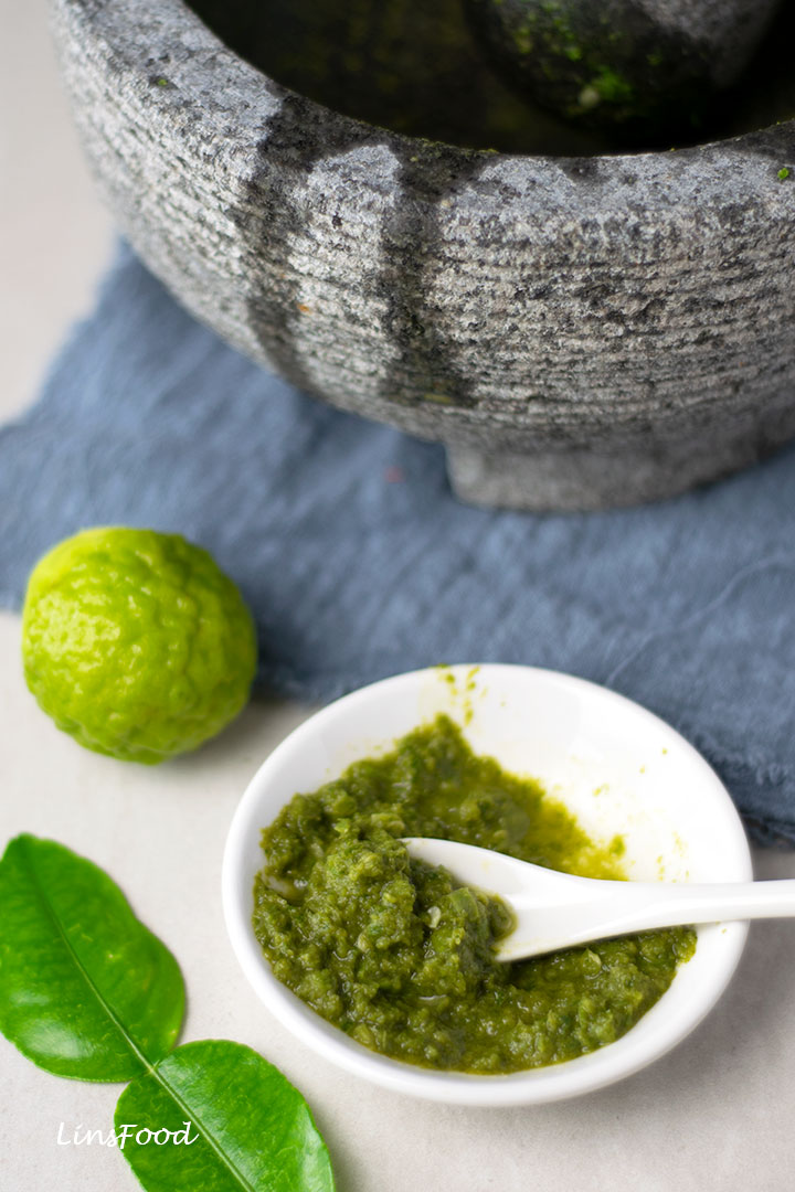 green chilli paste in white bowl with lime and lime leaves