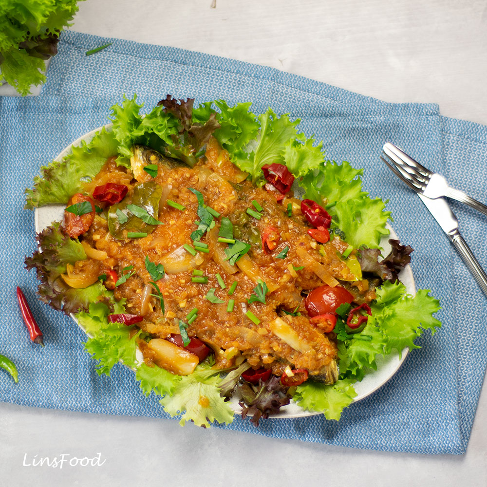 fish topped with red sauce on a bed of lettuce