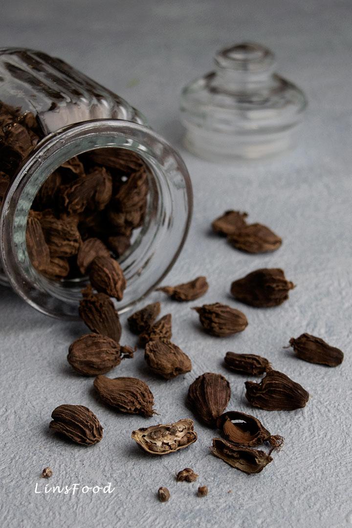 black cardamom spilling out of glass jar