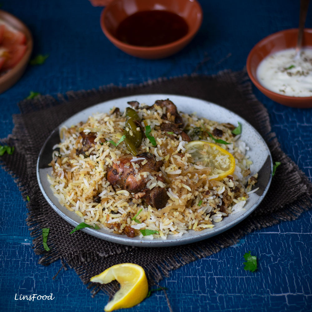 Chicken Biryani on a large plate with lemon slices