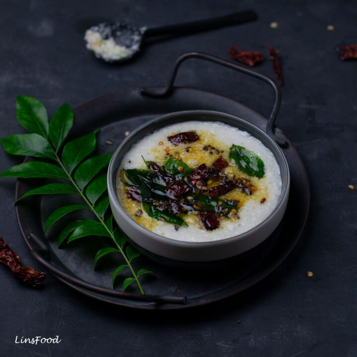 Coconut chutney in a grey bowl, topped with dried red chillies and curry leaves